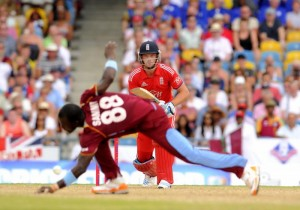 England's Jos Buttler drives a delivery past West Indies captain Darren Sammy.