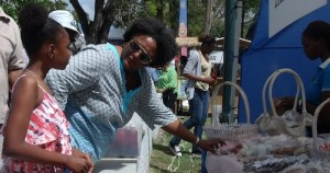 Leader of the Opposition, Mia Mottley, checking before purchase with young Sheridan Archer, at Treats Plus during her tour of Agrofest in Queens Park yesterday.