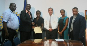 Rotary Club of Barbados West's 203-2014 Scholarship winner Shaneanoh Carter (third from left) accepting her award from Parliamentary Secretary in the Ministry of Education Senator Harry Husbands. Looking on (from left) are Rotary West's director of youth services Winfield King, Diamonds International managing director Jacob Hassid, Sandy Lane's public relations manager Aprille Thomas and Chief Education Officer  Laurie King.