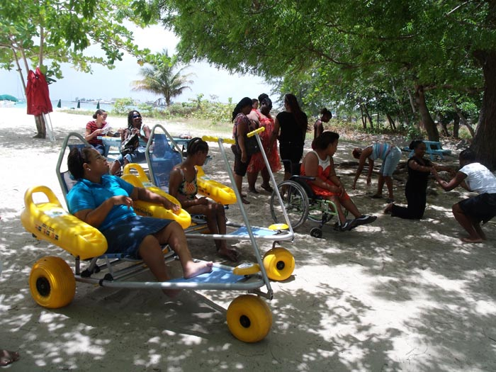 Deaf BCD Breakfast Club member Nakira Orisaja (in purple short pants) with counsellor Dr Dianne Brathwaite before taking to the sea at Brown's Beach, while others take a view from their beach wheelchairs.