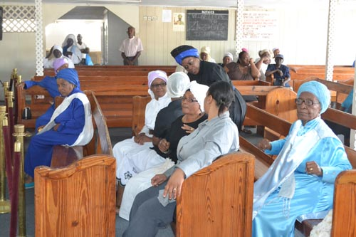 Members sitting quietly in the church, enjoying the recorded religious music.
