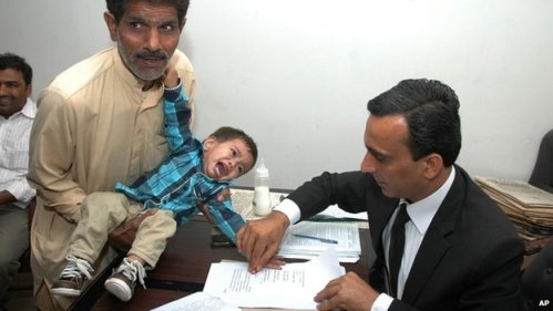 The young boy cried as he was made to provide fingerprints at a legal office in Lahore.