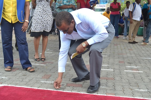 Jeffrey Bostic, Member of Parliament for City of Bridgetown laying silver coins.