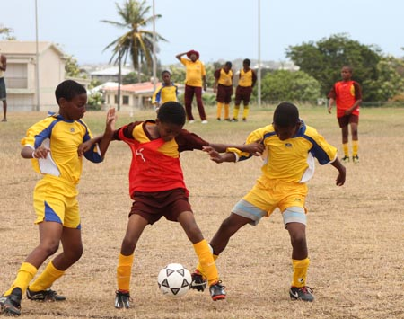 Hill Top Preparatory's left-wing Tajiri Sutherland (centre) being challenged by two St. John defenders.