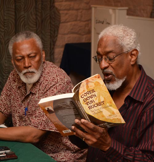 Elombe Mottley (right) reading an excerpt from his book Cover Down Yuh Bucket: The Story Of Sticklicking In Barbados. At left is Professor Linden Lewis.