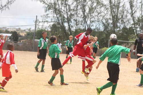 St Angela's goal-scorer Aren Spencer leaps high above his team-mates to make this headed clearance.
