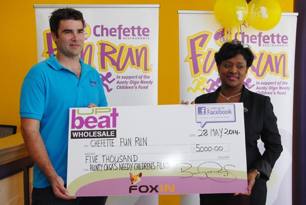 Director of UpBeat Wholesale  Barry Mayers presenting the cheque to Chefette's advertising manager Lisa Carter.