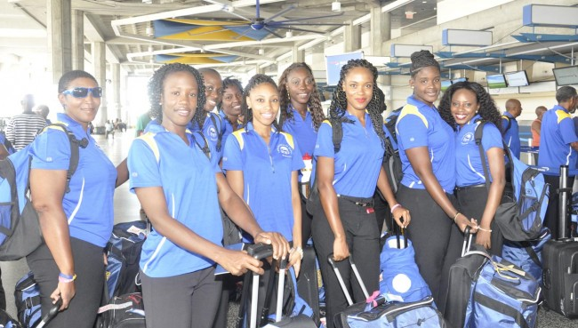 Barbados' netballers and assistant coach Sandra Bruce-Small (left) at the Grantley Adams International Airport this evening.