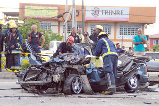 DESTROYED- Fire officers at the scene of yesterday's fatal accident on Uriah Butler Highway, Chaguanas, in which Nanda and Mahadeo Ramcharan and their son Nyron died. –Photo- KRISHNA MAHARAJ.