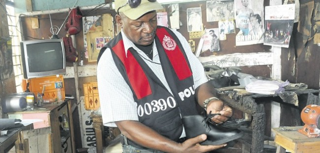 Detective Inspector Clarence Bailey of the Anti-Trafficking in Persons and Intellectual Property Vice Squad examines one of the fake Clarks shoes seized during yesterday's police operation in downtown Kingston.
