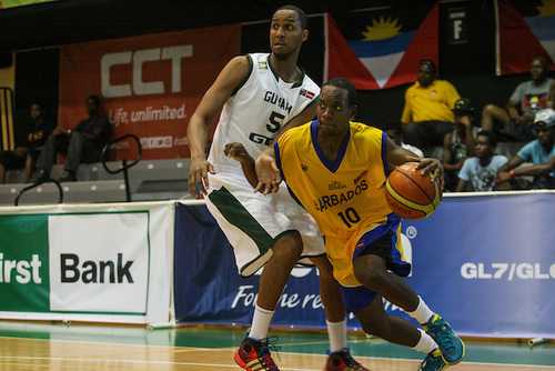 Keefe Birkett (with ball) driving to the basket during this evening's game against Guyana.