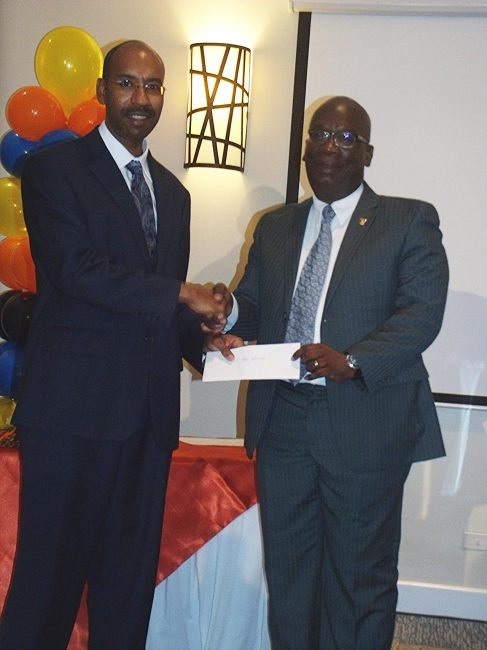 Top innovator Grenville Phillips (left) receiving his award from Minister of Education Ronald Jones.