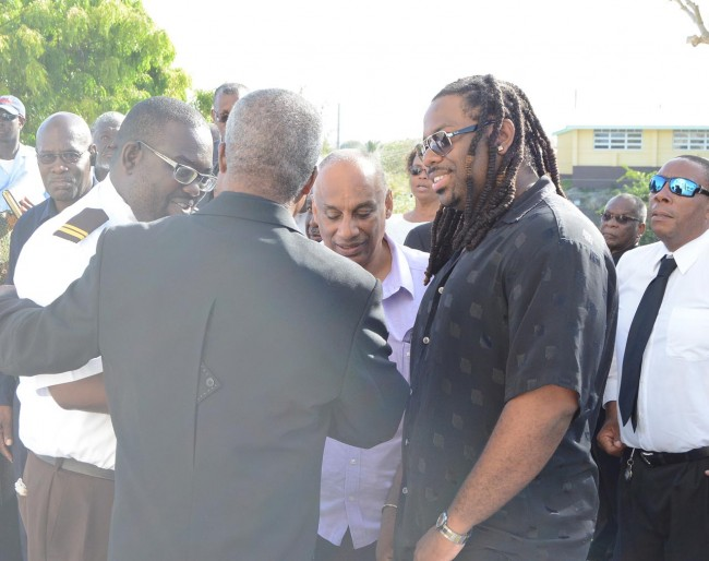 Calypsonians Mikey (right) and Ishaka (left)       in conversation with others after the funeral.