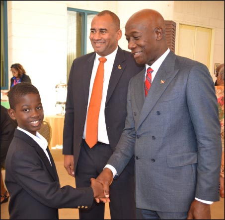 Acting Prime Minister Richard Sealy and Trinidad and Tobago's Opposition Leader Keith Rowley greet Junior Calypso Monarch Raanan Hackett who performed at this morning's opening of the Caribbean Parliamentary Association's conference.