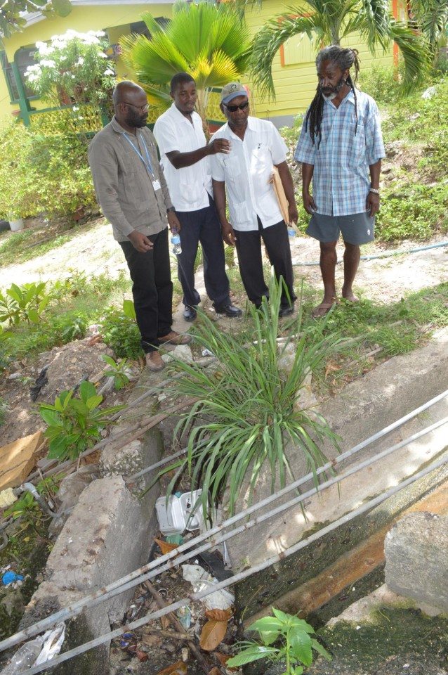 Tyrone Applewhaite (left), chief environmental health officer and environmental officers Kenvil Rogers (second from left) and Stanley Alleyne (second from right), along with resident Hal Jones looking at a blocked drain in Licorish Village, My Lord's Hill.