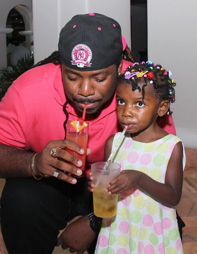 Mikey drinking a glass of juice, along with his little fan Saniyah at her birthday party.