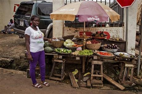 A trader posing for a photograph at her food stall in the city of Freetown, Sierra Leone, today.