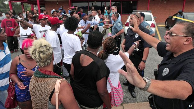 Ferguson police officers try to calm down a crowd near the scene of the shooting on Saturday.