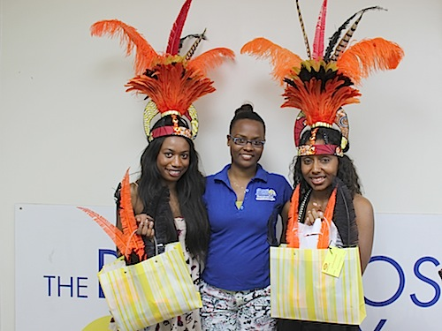 Satta Bockarie (l) and Satya Collymore (r) receives her costume from Terriesha Niles, a representative of Barbados TODAY's Sales and Marketing Department.