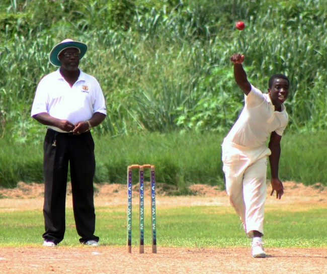 Offbreak bowler Kerry Justin sending down another delivery during his five-wicket haul.