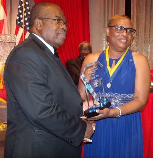 Outgoing Kiwanis of Bridgetown president Ken Knight (left) presenting Jennifer Hinkson with the Kiwanian Of The Year award. In background is Prime Minister Freundel Stuart.