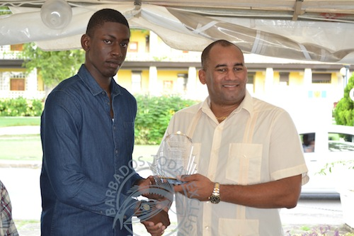 Gershon Shepherd being presented with his award by Minister of Tourism Richard Sealy.