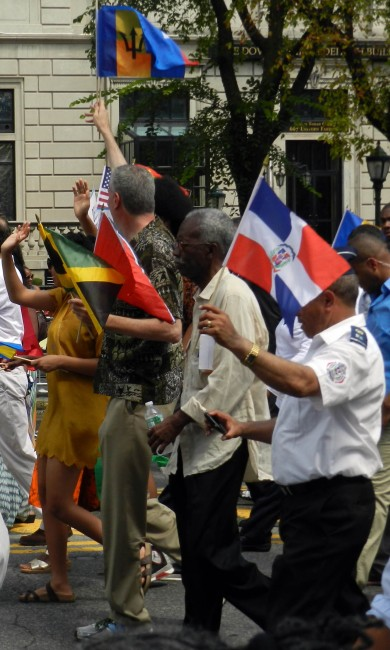 New York's Mayor Bill de Blasio holding high the Barbados Flag.
