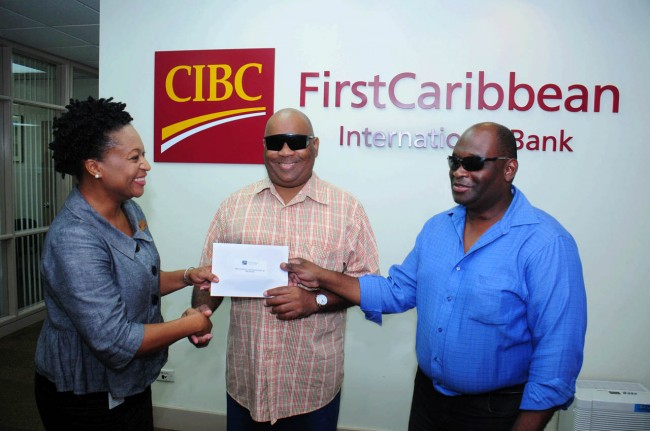 Nicole Weekes of CIBC FirstCaribbean presents Rudyard Welch, president, and Roger Vaughan, vice president of the National United Society for the Blind with a contribution for the society's education and sports fund.