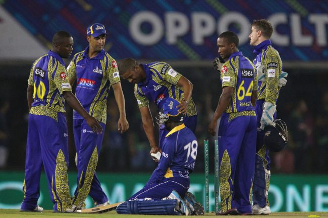A distraught Jonathan Carter (kneeling) is consoled by the Cobras players after the Barbados Tridents finally lost the match in the Super Over.