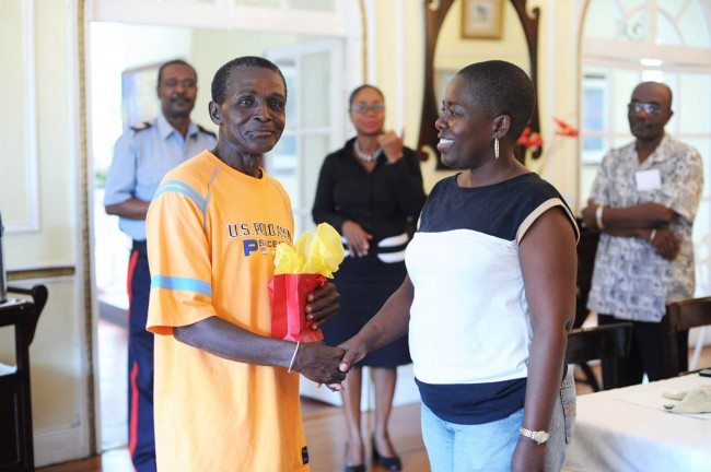 McDonald Thornhill accepting  a farewell gift from Angela Griffith of the housekeeping department at Ilaro Court.