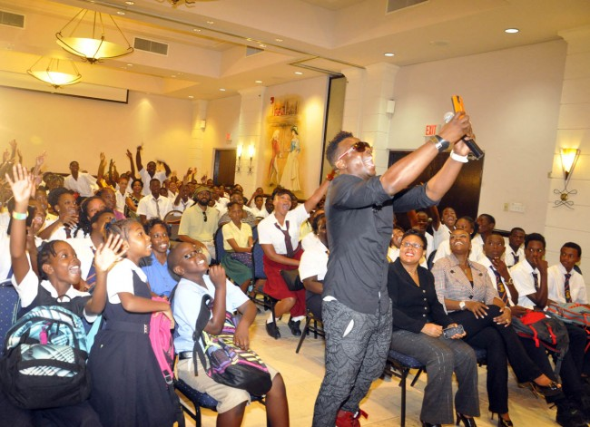 Singer Dwaine Antonio taking a selfie with enthusiastic students.