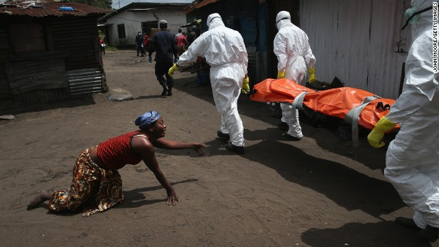 A woman crawling toward the body of her sister as a burial team takes her away for cremation Friday, today, in Monrovia, Liberia.