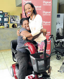 Physically challenged Correta Vincent is overcome with joy as she embraces programme manager for special needs at Digicel Foundation Judene Hunter.