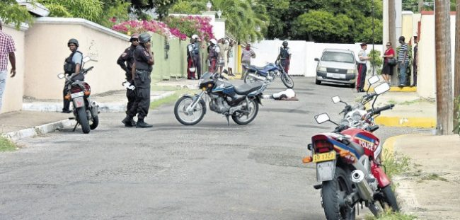 Police at the scene of yesterday's murder of a man by gunmen on Kensington Crescent on the outskirts of New Kingston.