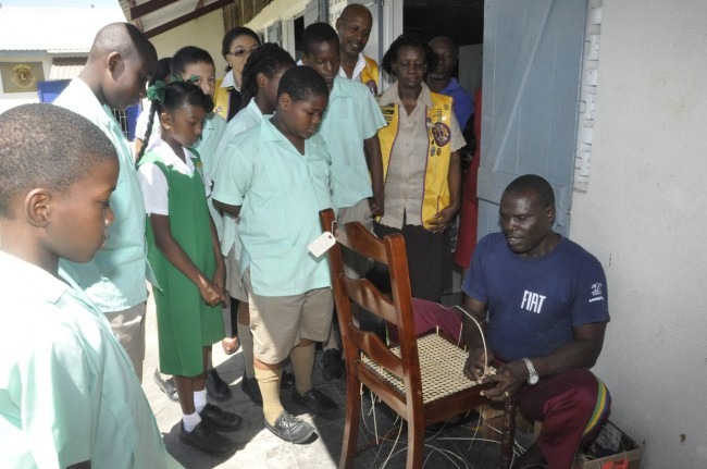 Trainee Granville Carter demonstrating the process of caning a chair to students and Lion members.