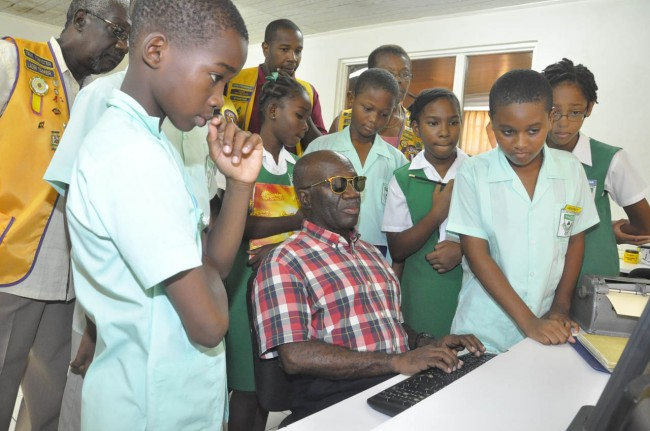 President of the Barbados Association for the Blind and Deaf Elviston Maloney in the centre's computer lab speaking to students about the specialized software.