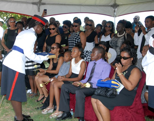 Inspector Christine Stanford presenting Sergeant David Leacock's daughter Teal (third left) with one of his awards, as she sits among his wife Michelle (left), son Taurel (second left) and daughter Davelle (right), at the graveside.