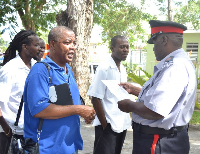 General secretary of the Unity Trade Union Caswell Franklyn has a word with this police officer while on the picket line today.