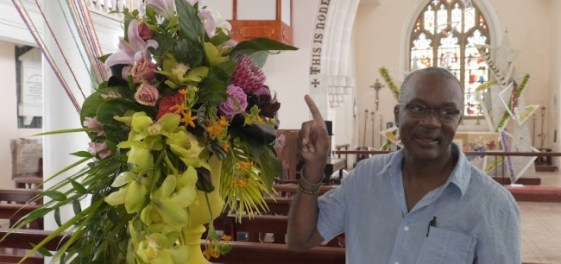 Reverend Peter Haynes talks about one of the floral arrangements.