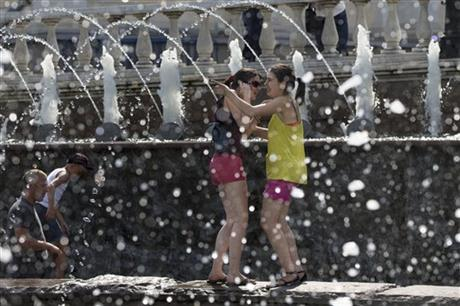 In this July 30, 2014 file photo, girls cool themselves in a fountain after a sunny and hot day in Alexandrov Garden at the Kremlin Wall in Moscow, Russia.