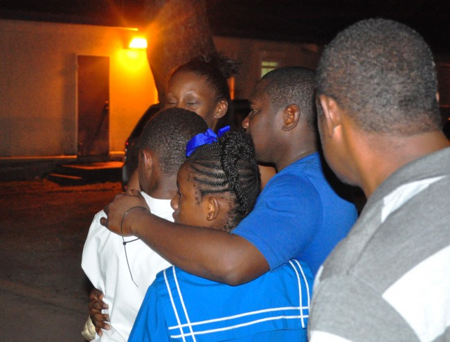 Kemar Trotman (in blue) embraced his family when he arrived at the District A Police Station.