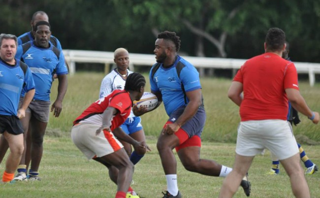 Marlo Sandiford (with ball) of Scorpions looks to power past Emperors' David Burke (red shirt).