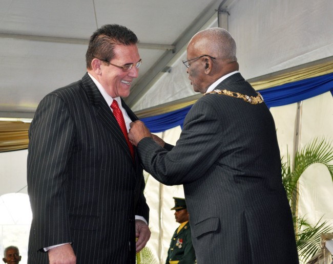 Regional Broadcaster, Vic Fernandes, has his award pinned to his lapel by  Governor General, Sir Elliott Belgrave.
