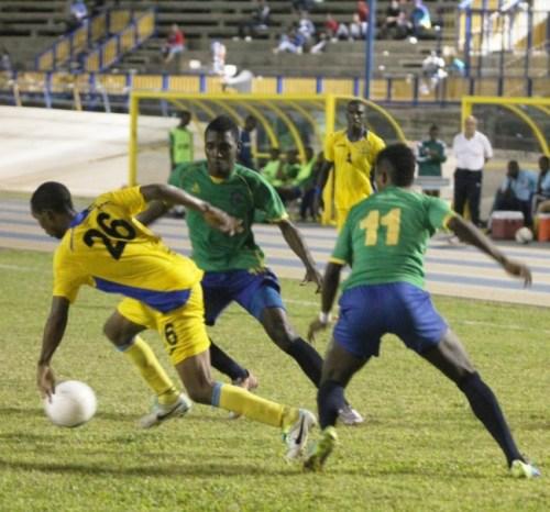 Barbadian midfielder Hadan Holligan (left) dribbles past two Vincentian defenders.