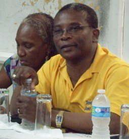 Pine branch chairperson, Undine Whittaker (right), takes notes as Housing Minister, Dennis Kellman, speaks on housing developments.