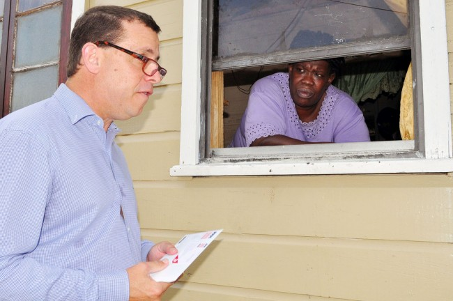 Innotech chairman Anthony DaSilva  chatting with the needy Harriett Hackett  at her My Lord's Hill home this morning.