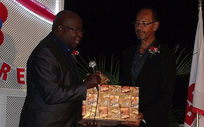 Postmaster General (ag), Nigel Cobham (L), presents a retirement gift to outgoing Postmaster General, Jewel Brathwaite.