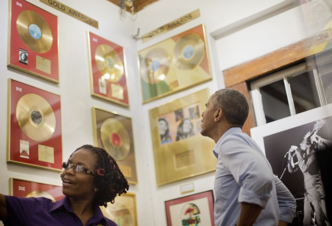 U.S. President Barack Obama, right, looks at selection of Bob Marley's gold records during his unannounced visits to the Bob Marley Museum led by tour guide Natasha Clark, left, Wednesday, April 8, 2015 in Kingston, Jamaica. (AP Photo/Pablo Martinez Monsivais)