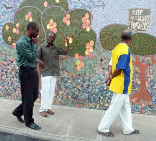 NIS Chairman Dr Justin Robinson (left) walking with a visitor of the mural.