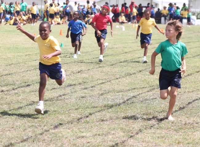 Adan Clarke (left) of Yellow House ran away from the field in the under-nine boys' sprint.
